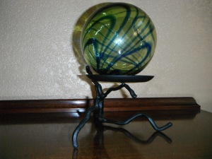 Green glass ball on creepy tree stand